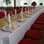 Zastawiony stół weselny udekorowany wzłoto czerwonych barwach