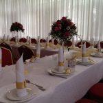 Stół weselny udekorowany bukietami kwaiatów izłotymi akcentami