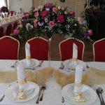 Sala weselna zastawiona iudekorowana bukietami kwiatów